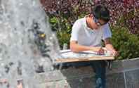 Photo of a student sitting in front of a fountain